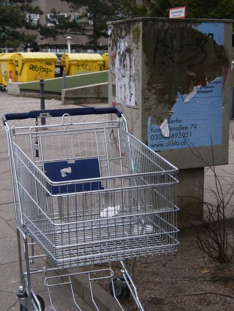 einkaufswagen, mülltonnen und plakat